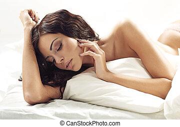 Fresh young woman lying on the huge bed