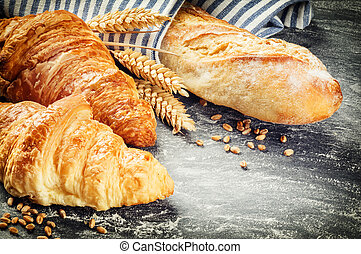 Freshly baked baguette and croissants in rustic setting