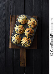 Freshly baked blueberry muffins on oak board on black background with natural lighting top view