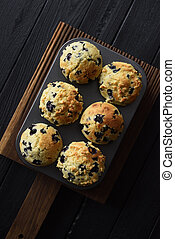 Freshly baked blueberry muffins on oak cutting board on black background with natural lighting top view