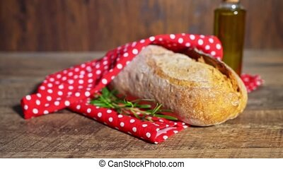Freshly baked bread wrapped in red towel.