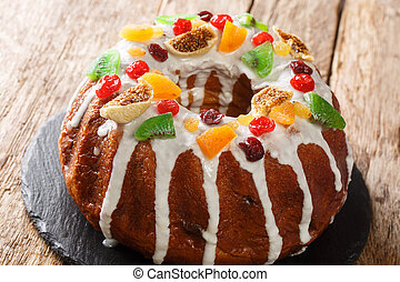 Freshly baked cake with raisins, dried apricots, dried cherries, kiwi and cranberries and icing close-up on a board. horizontal