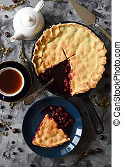 Freshly baked cherry pie with black tea on dark background top view. Low key still life with natural lighting