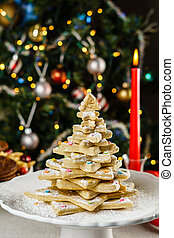 freshly baked christmas tree shape cookies on a table with blurred background.