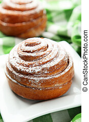 Freshly baked cinnamon buns on white plate