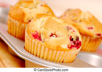 Freshly baked cranberry muffins resting in a muffin pan