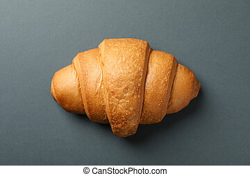 Freshly baked croissant on dark background, top view
