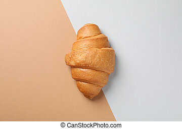 Freshly baked croissant on two tone background, top view