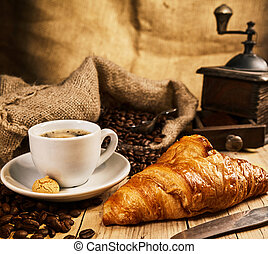 Freshly baked croissant with a cup of coffee