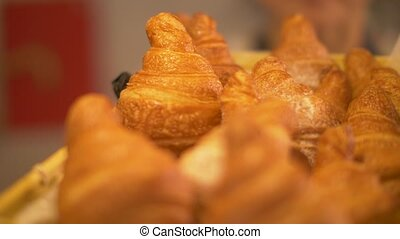 Freshly baked croissants from puff pastry in straw basket in...