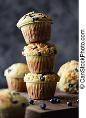 Freshly baked crumble muffins with wild bilberries arranged in unstable pile on dark background copy space. Low key still life with natural lighting