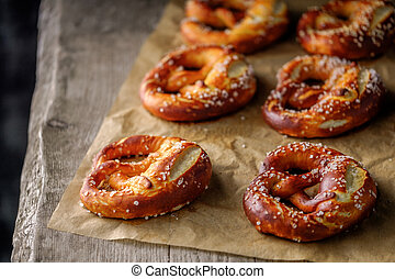 Freshly baked home soft pretzel with salt on craft paper for...