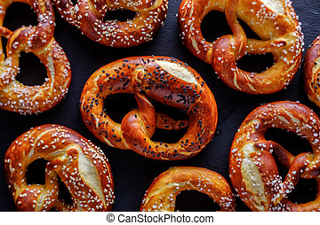 Freshly baked homemade soft pretzel with salt on dark rustic...