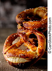 Freshly baked homemade soft pretzel with salt on rustic...