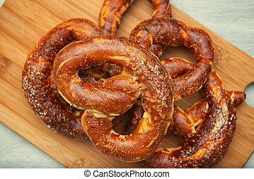 Freshly baked homemade soft pretzel with salt on wooden cutting board