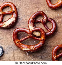 Freshly baked salted pretzel on wooden background. Beer snack. Top view.