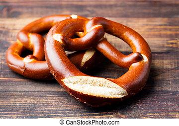 Freshly baked soft pretzel from Germany on wooden background