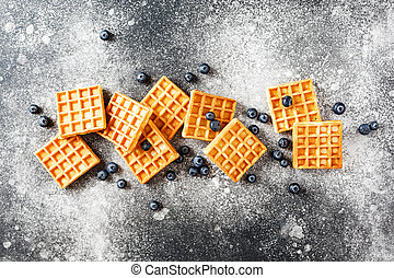 Freshly baked waffles and blueberries on a textured surface.
