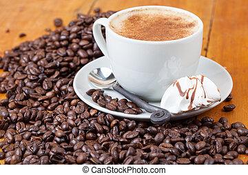 Freshly brewed cup of coffee served with meringue between...