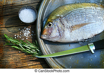 Freshly caught fish on cooking platter with sea salt and ...