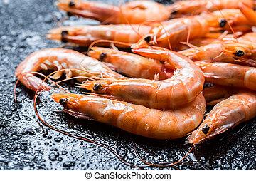 Freshly caught shrimp on black rock