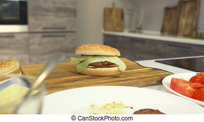 Freshly cooked cheeseburger lies on the kitchen board in the...
