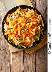Freshly cooked French fries baked with cheddar cheese, bacon and parsley closeup. Vertical top view