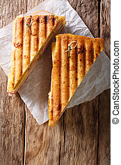 Freshly cooked grilled sandwich with meat and cheese, close-up on paper on the table. Vertical top view