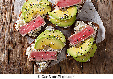 Freshly cooked sandwiches with fried tuna, avocado and cream cheese close-up. horizontal top view