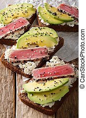Freshly cooked sandwiches with fried tuna, avocado and cream cheese close-up. vertical