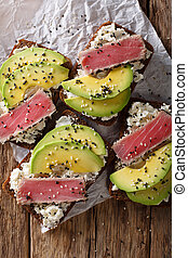 Freshly cooked sandwiches with fried tuna, avocado and cream cheese close-up. Vertical top view