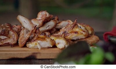 Freshly cooked smoked chicken wings on wooden platter. Bbq theme. Slow motion camera movement. Pan shot