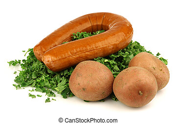 freshly cut kale cabbage, some potatoes and a smoked sausage, the ingredients for making traditional Dutch kale and potato stew on a white background