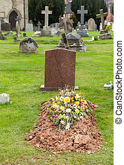 Freshly dug grave in cemetery - Flowers on the top of a...