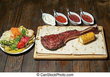 Freshly grilled Tomahawk steaks on wooden cutting board with vegetables and sauces