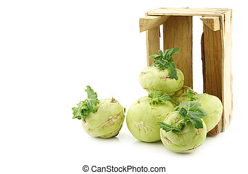 Freshly harvested kohlrabi with some foliage in a wooden crate