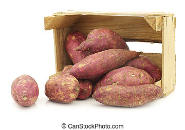freshly harvested sweet potatoes in a wooden crate