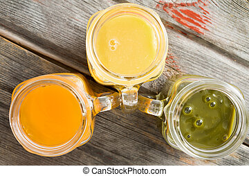 Close up overhead view of a trio of glass jugs filled with freshly liquidised tropical fruit juice including orange, mango and a kiwifruit blend on an old wooden table