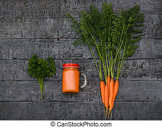 Freshly made carrot smoothie and bunch of carrots on a rustic table. The view from the top. Flat lay.