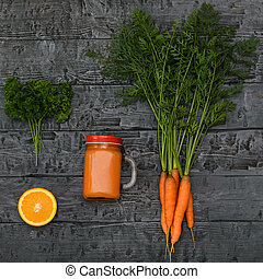 Freshly made carrot smoothie, bunch of carrots and orange on a rustic table. The view from the top. Flat lay.