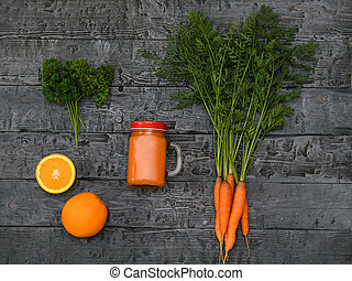 Freshly made carrot smoothie, bunch of carrots and two orange on a rustic table. The view from the top. Flat lay.