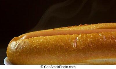Freshly made hot dog against black background. Worldwide popular fast food. 4K macro dolly shot