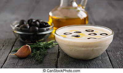 Freshly made tzatziki in a glass bowl with garlic and dill on a dark wooden table.
