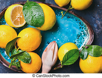 Freshly picked lemons with leaves and pounder in blue plate...