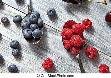Delicious sweet berries on a spoon gray wooden background. Flat lay. Concept of vegetarian eating.