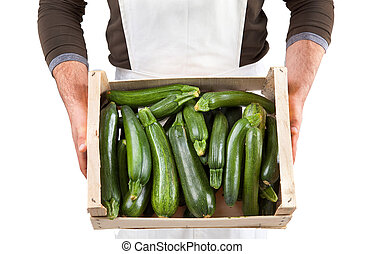 Freshly picked zucchini in a wooden box with greengrocer