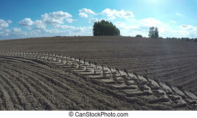 Freshly plowed agriculture farm field in autumn with tractor traces. Time lapse