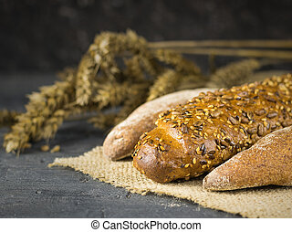 Freshly prepared baguettes on a piece of burlap on a dark table with ears.