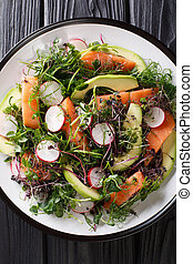 Freshly prepared salad of red fish, avocado, radish and a mix of micro green close-up on a plate. Vertical top view