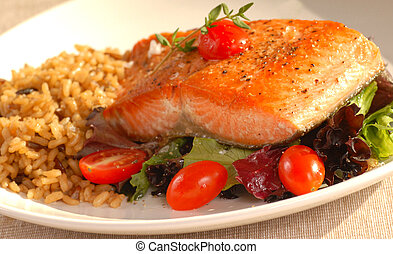 Freshly seared piece of salmon resting on a plate of greens with brown rice and tomatoes